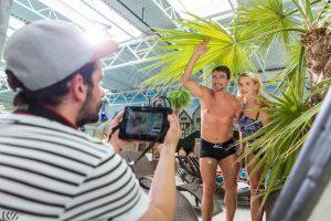 ujęcie z planu reklamy telewizyjnej dla aquapark reda aktorzy pod palmą